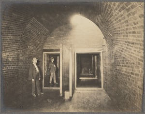 Men standing in divided sewer