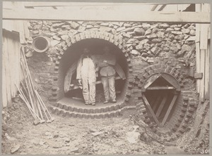 Men standing in opening of unfinished sewer