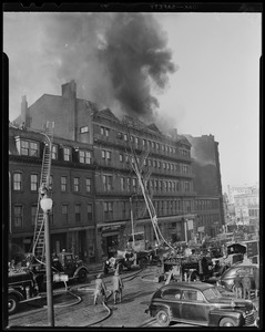 Building on fire with fire department ladders