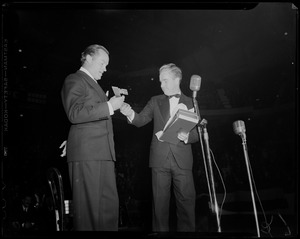 Acting Mayor of Boston John E. Kerrigan presenting object, possibly a symbolic key, to Bob Hope on stage