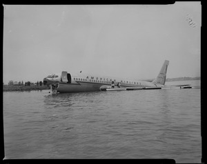 American Airlines airplane in Boston Harbor, with two men sitting on the wing and one in a boat alongside