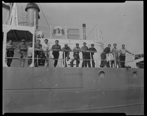 Group of 13 posing on deck of Liberian freighter Alberta, anchored off Cape Cod canal, after Captain Gerasimos Potamianos was overpowered by the crew following his murder attempt on Elefehrios Metaxes