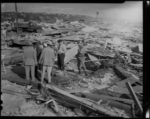 Group of men, some in uniform, standing at wreckage site with box of human bones