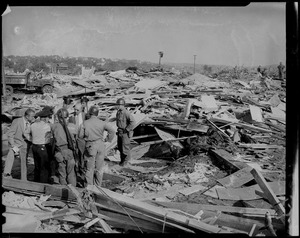 Group of men, including some in uniform, standing amid damage beside a box full of human bones