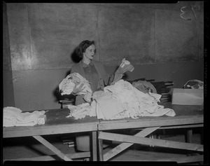 Woman going through clothing drive items
