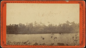 View of an unidentified body of water (in foreground) and a house partially visible on the opposite shore
