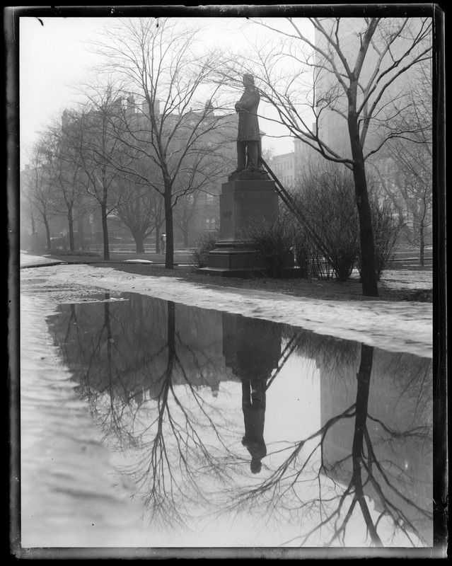 Thawing in the Public Garden showing Summers' statue reflecting in puddle of water on Boylston St. side of the Garden