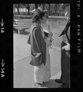A woman talking to and handing a pamphlet of A.C. Bhaktivedanta essays to a man
