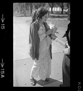 A woman talking and holding a stack of pamphlets of A.C. Bhaktivedanta essays