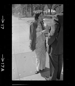 A woman talking with a man and holding a stack of pamphlets of A.C. Bhaktivedanta essays