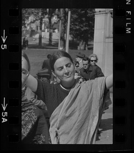 A woman with a scarf wrapped around her and holding her arms open wide