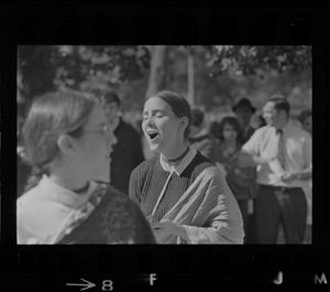A woman singing outside with spectators in the background