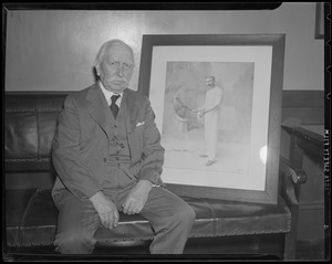 Thomas Pettitt, tennis great, sits with photo of himself in his prime