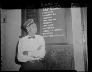Porter stands next to Shore Line Express sign, South Station