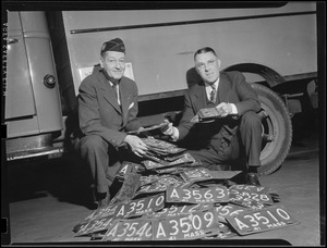 WWII: Two men with pile of licenses donated for scrap (war effort)