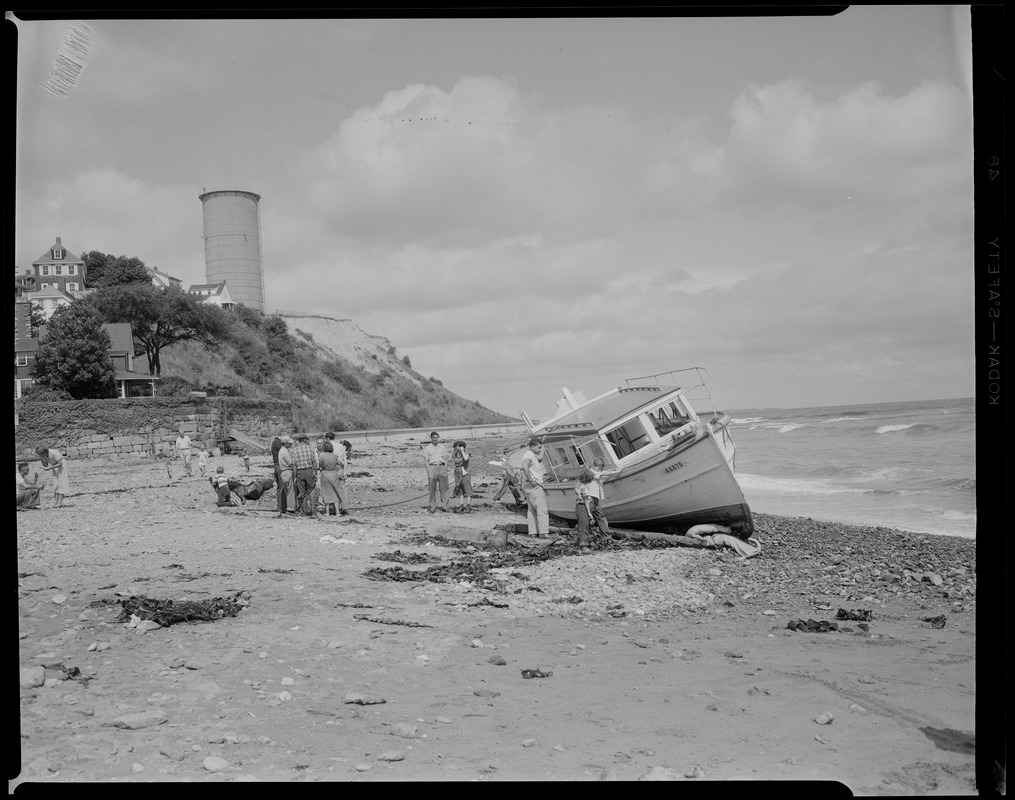 Boat ashore on Winthrop Beach. Water tower on Cottage Hill in background. Yirrell Beach now, water tower in back, 'Greathead' (Cottage Hill) old Green Hill.