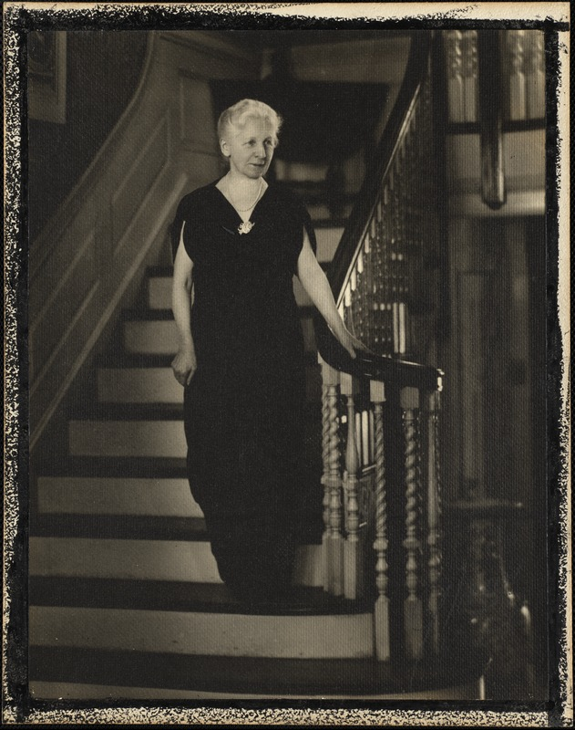Helen Temple Cooke dressed in black velvet, pearls, and fancy brooch descending a staircase