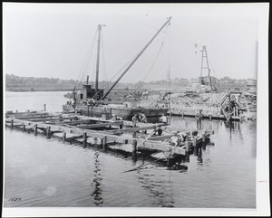 Men in a harbor, working on a pier