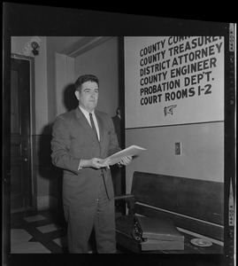 Assistant District Attorney Donald Conn with folio in front of directional signage at the courthouse