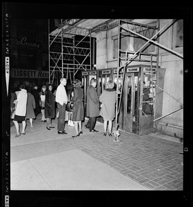 Group of people gathered on the sidewalk in front of phone booths during the blackout