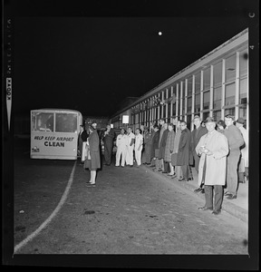 Group of people standing outside an airline at the airport