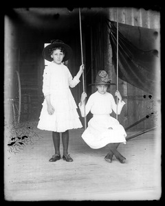 Two unidentified young women, one sitting on swing