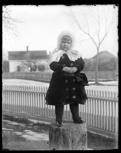 Unidentified child standing on tree trunk