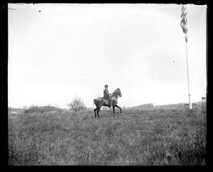 Unidentified man on horseback in field and flagpole