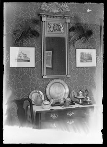 Scene of one wall in dining room of a home with bureau, mirror and pictures