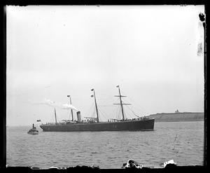 Four masted ship and tugboat in harbor