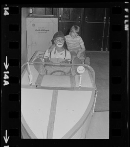 Clown sitting in a boat with child