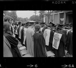 Group of Brandeis University graduates wear clenched fist, the symbol of student resistance, on the back off their robes during commencement