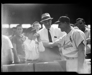 Young fan takes Stan Musial's picture as Comm. Ford Frick looks on
