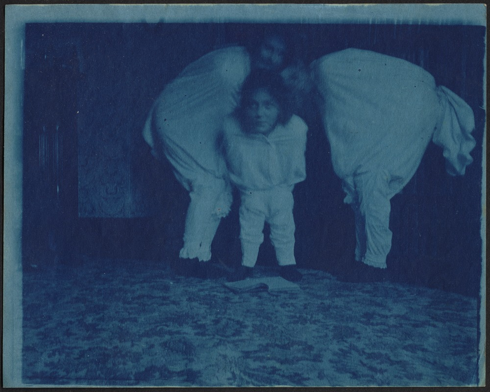 Abstract photo of three children (Isabel Stevens in middle) in white costumes, huddled together