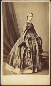 Young woman in satin dress with wide sleeves; standing near chair