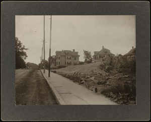 Residential street with some excavation work in the foreground and houses in the background