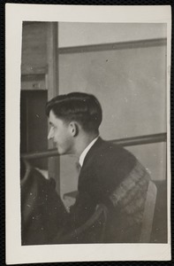 Young man, seated, from side