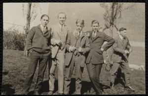 Four young men posing, another behind them