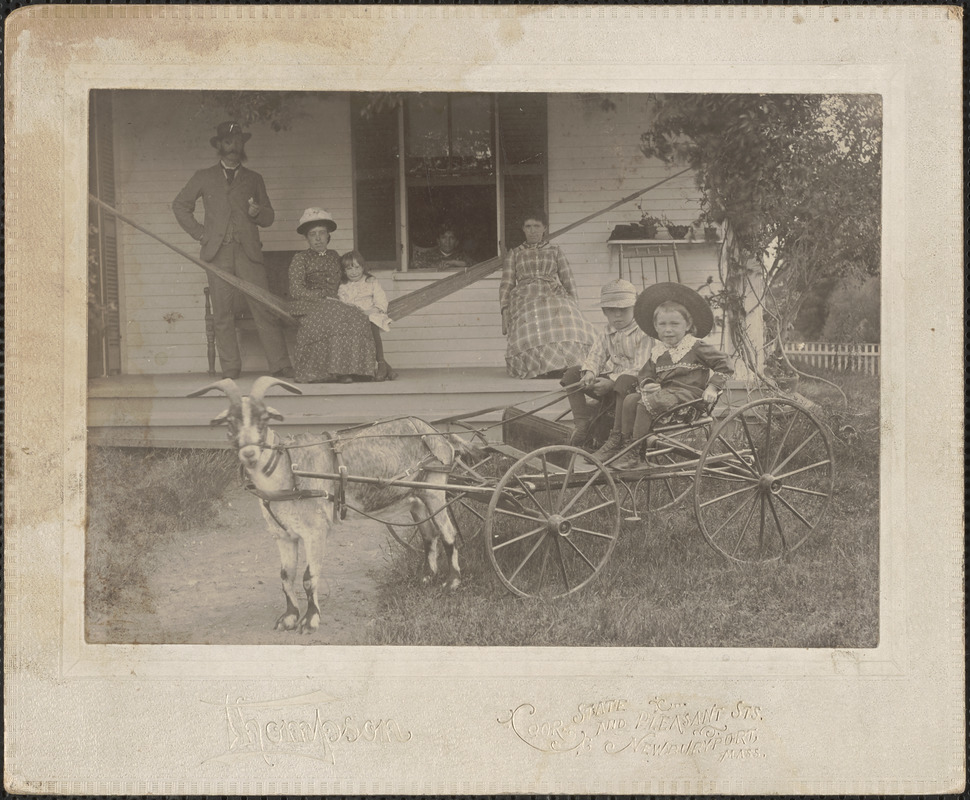 Adults and child on house porch, goat pulling children on carriage, c. 1900