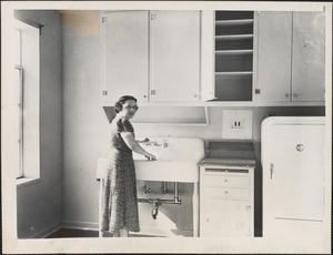 A young woman inspects the modern kitchen in one of the East Cambridge federal apartments which will be finished next week