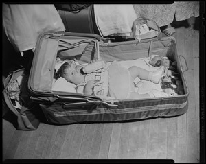 Child laying in makeshift bed with bottle