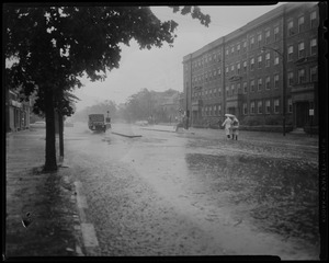 Couple with umbrella walking on a flooded street