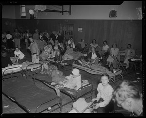 Children and adults on cots and folding chairs at a gymnasium shelter