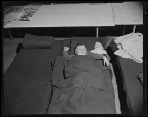 Child with a doll, sleeping on a cot at a shelter