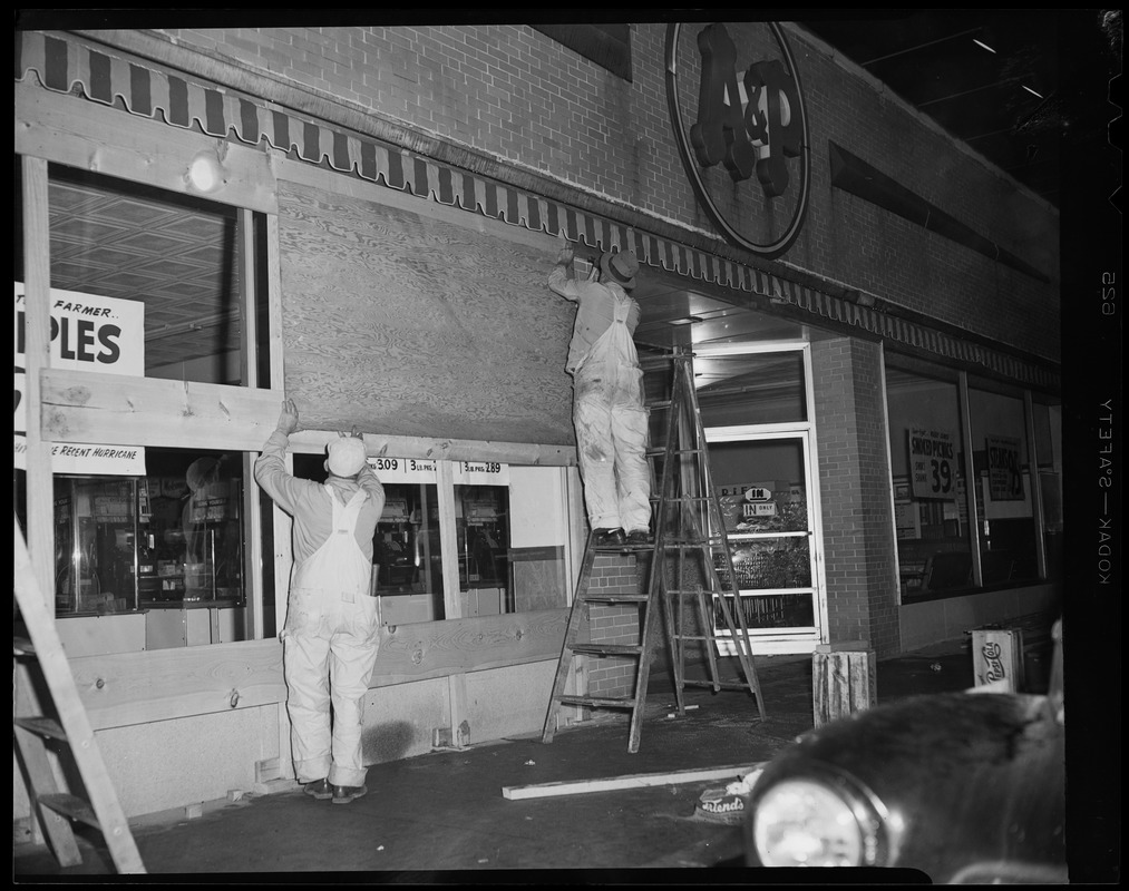 Two men boarding up the A & P in preparation for the hurricane