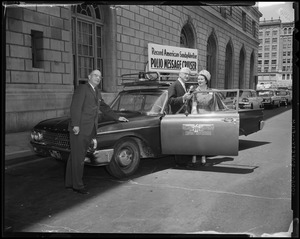 Dr. Albert B. Sabin (middle) and two others stand next to the Record American-Sunday Advertiser Polio Message Cruiser