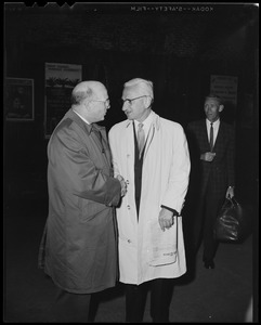 Dr. Albert B. Sabin (right) shaking hands with a man while another looks on
