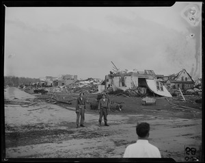 Two military men, standing in front of a string of destroyed homes
