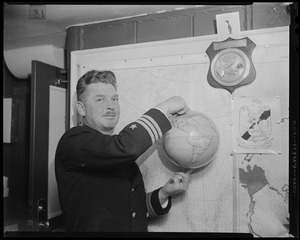 Navy officer holding the globe with his two pointer fingers