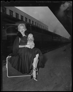 Eva Gabor, seated with her dog Delilah on her lap